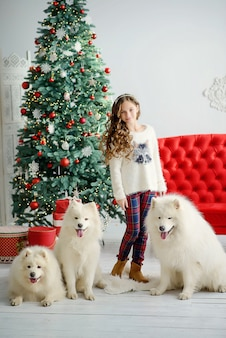 Little beautiful girl model and three large white fluffy dogs near the christmas tree in the new years interior with a red sofa.