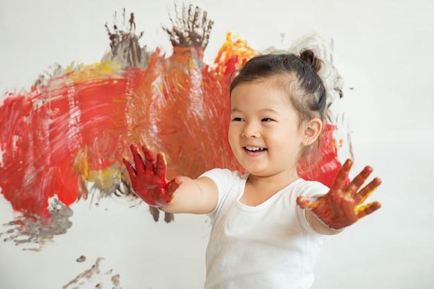 Маленькая красивая девушка азиатской внешности в белой футболке улыбается размазанными краской руками на фоне окрашенной стены.