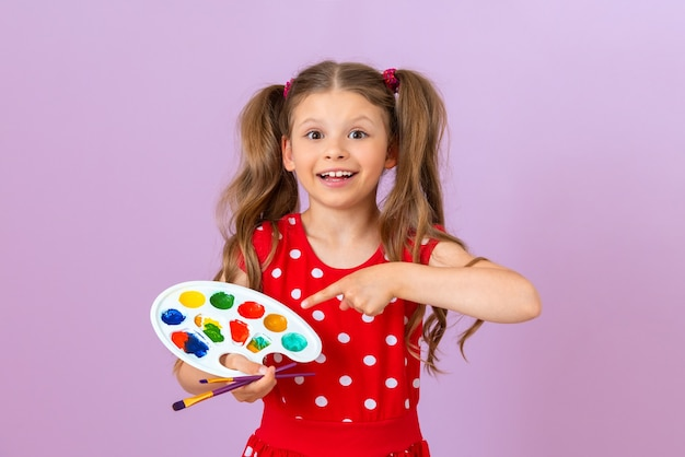 A little beautiful girl in a red dress is holding a paint palette and a paint brush.