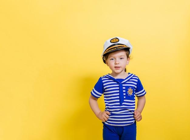 黄色いスペースの美しい少女船乗り。キャップ付きセーラースーツのかわいい女の子がコピースペースの孤立したスペースに見える