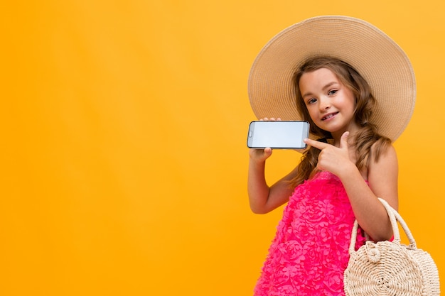Little beautiful girl on shopping against the background of the orange wall in a straw hat points to a blank phone screen