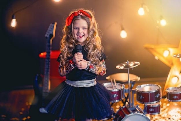 Little beautiful girl singing in recording studio