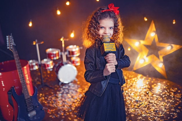 Little beautiful girl singing in recording studio
