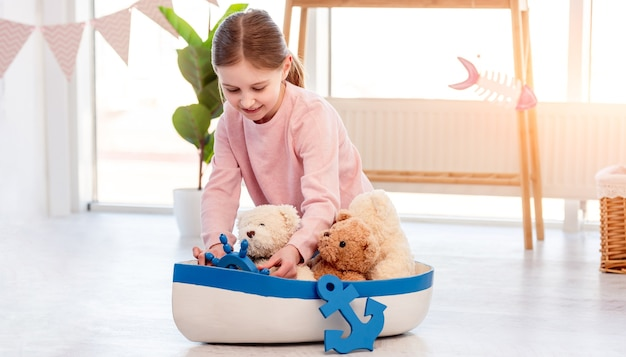 Little beautiful girl sitting on the floor and playing with toy ship in sunny room