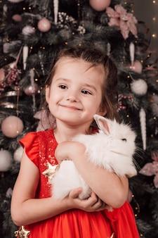 어린 아름다운 소녀는 미소를 지으며 크리스마스 트리 근처에서 그녀의 팔에 하얀 솜털 토끼를 안고 있습니다