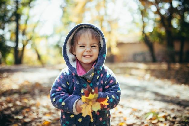Маленькая красивая девочка улыбается и играет с желтыми осенними листьями