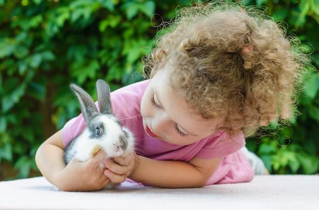 Маленькая красивая девушка улыбается, обнимая кролика на траве летом. счастливый смех ребенок и домашнее животное, играя на открытом воздухе. кролик - символ пасхи.