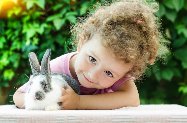 Little beautiful girl smiling, hugging a baby rabbit on the green in summer. happy laughing child and pet playing outdoors.
