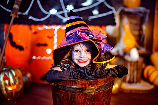 A little beautiful girl in a witch costume celebrates at home in an interior with pumpkins and cardboard magic house on the background smiling and looking at camera.