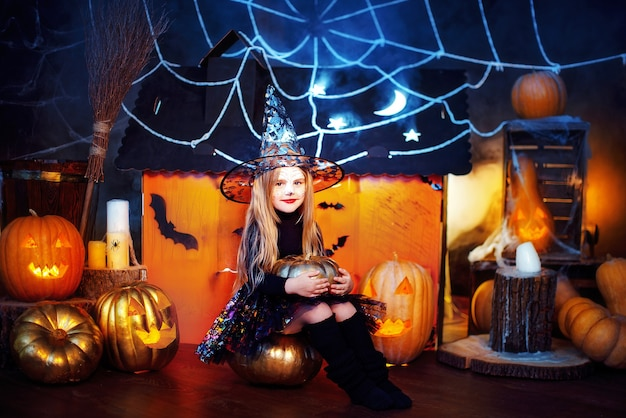 A little beautiful girl in a witch costume celebrates at home in an interior with pumpkins and cardboard magic house on the background.