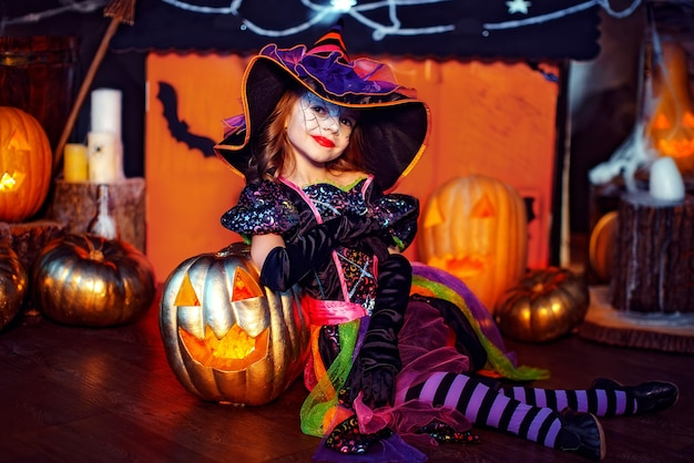 A little beautiful girl in a witch costume celebrates at home in an interior with pumpkins and cardboard magic house on the background