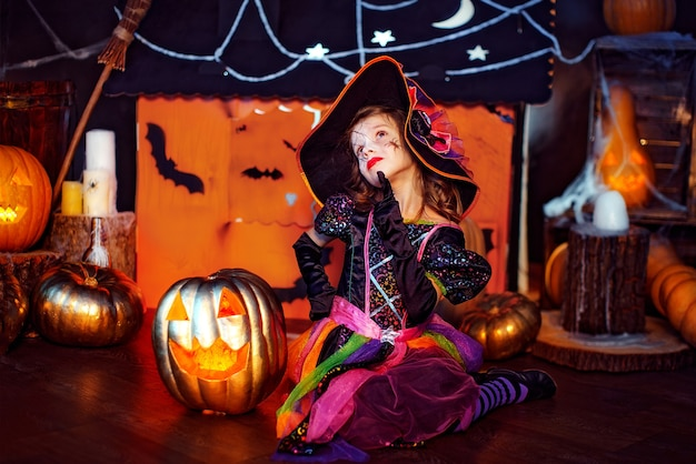 Little beautiful girl in a witch costume celebrates at home in an interior with pumpkins and cardboard magic house on the background