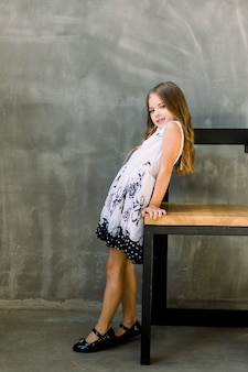 A little beautiful girl with brown hair in a white dress stands back to a wooden chair