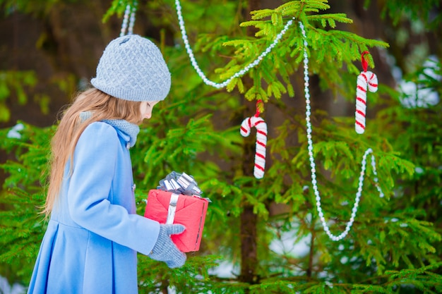 Little beautiful girl with christmas box gift in winter day outdoors. new year coming soon
