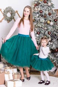 Маленькая красивая девочка с мамой в зеленых одинаковых юбках стоят возле елки