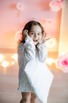 Little beautiful girl with light pillows in a cozy room