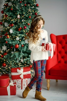 Little beautiful girl with long blond hair stands beside a christmas tree in the new years interior and holds a red box with a gift in her hands.