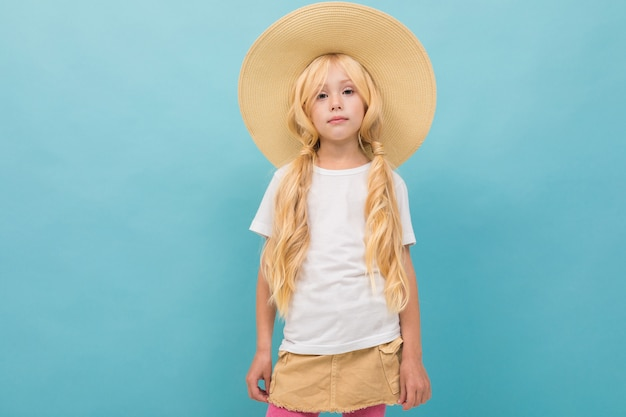 A little beautiful girl with long blonde hair braided in tails in big fair hat isolated on blue background