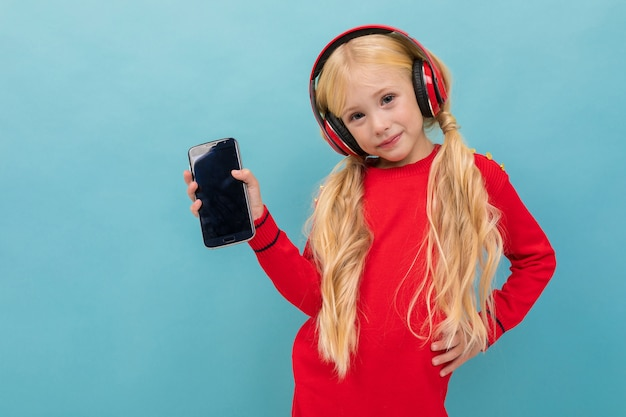 A little beautiful girl with long blonde hair braided in tails listen to music with big earphones isolated on blue background