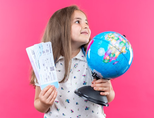 Little beautiful girl with long hair with backpack holding globe and air tickets looking aside with smile on happy face standing over pink wall
