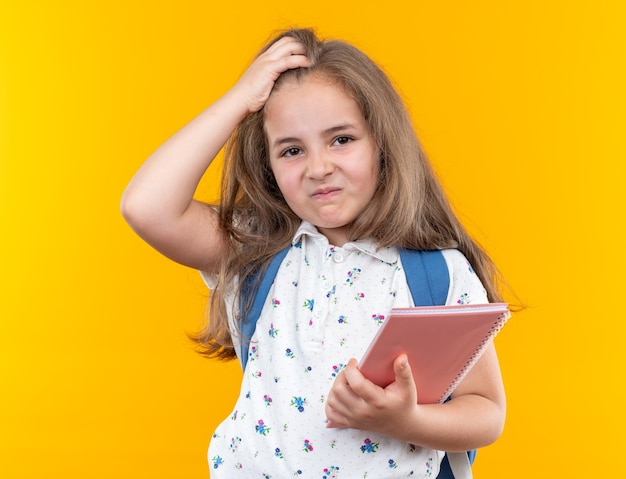 Little beautiful girl with long hair with backpack holding notebook confused with hand on her head standing on orange