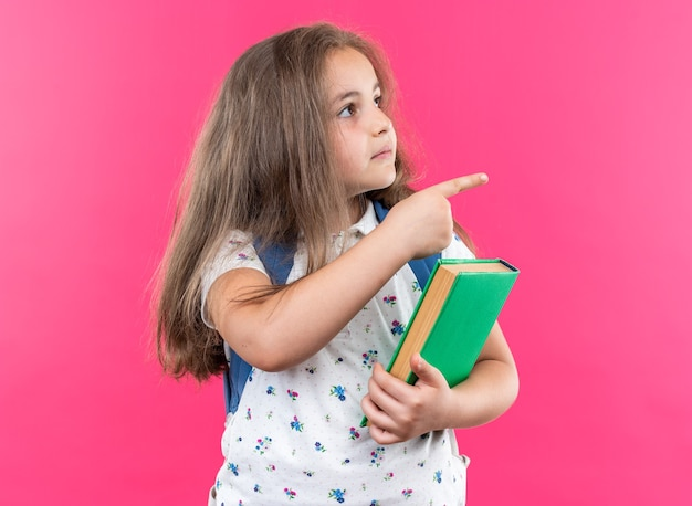 Little beautiful girl with long hair with backpack holding notebook looking aside with smile on face pointing with index finger to the side standing on pink