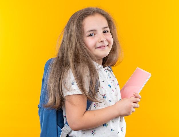 オレンジ色の壁の上に元気に立って幸せで前向きな笑顔の前を見てノートを保持しているバックパックと長い髪の少女