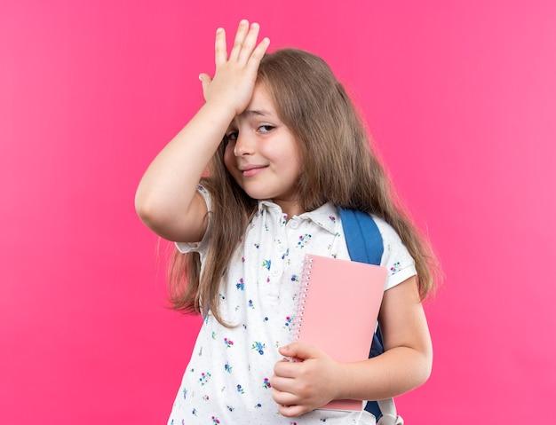 Piccola bella ragazza con i capelli lunghi con lo zaino che tiene il taccuino che sembra confusa tenendosi la mano sulla fronte per errore in piedi sul rosa