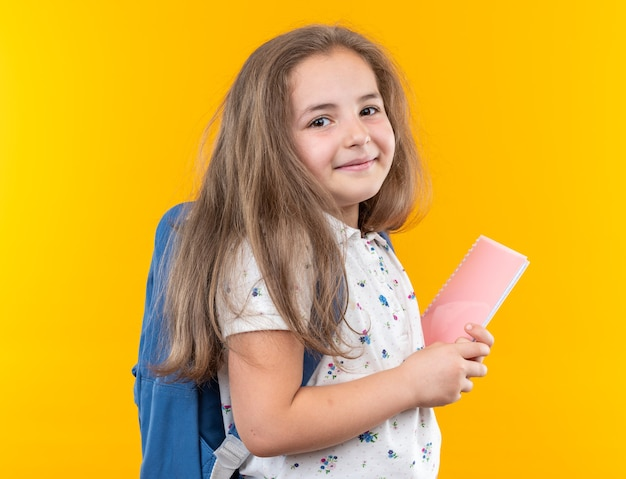 Little beautiful girl with long hair with backpack holding notebook looking at front happy and positive smiling cheerfully standing over orange wall