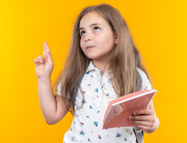 Little beautiful girl with long hair with backpack holding notebook looking up smiling pointing with index finger at something standing over orange wall