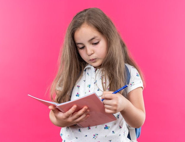 Little beautiful girl with long hair with backpack holding notebook and pen looking confident standing on pink