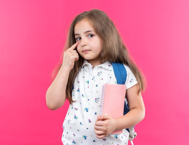 Little beautiful girl with long hair with backpack holding notebook pointing with index finger at her eye looking at front with serious face standing over pink wall