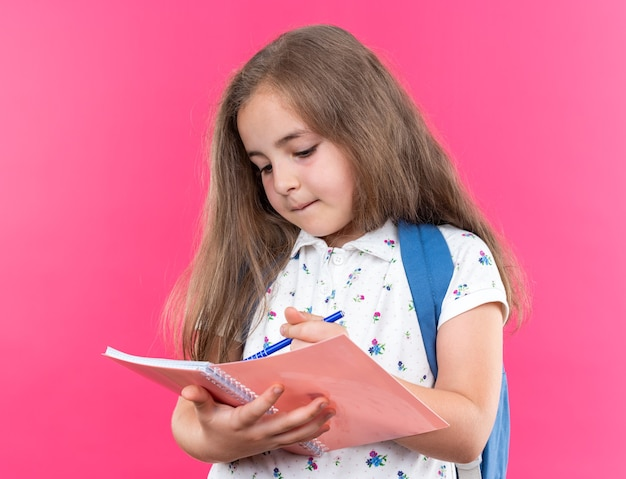 Little beautiful girl with long hair with backpack holding notebook writing something in it with pen looking confident standing on pink