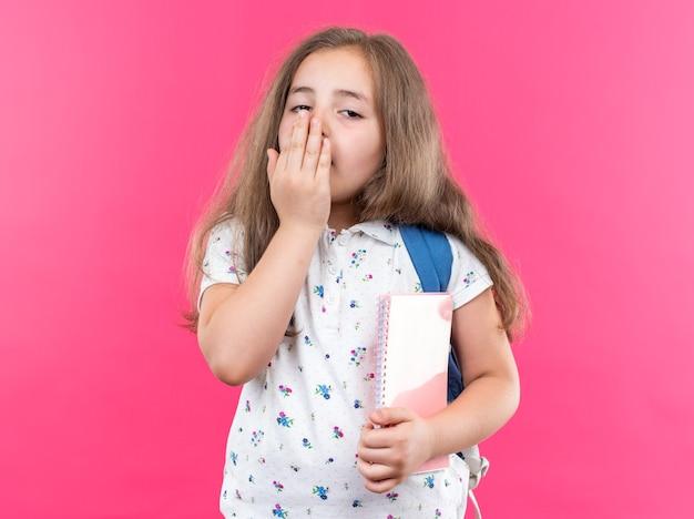긴 머리에 스마트폰을 들고 배낭을 메고 분홍색 벽 위에 손으로 서서 입을 가리고 피곤하고 지루한 하품을 바라보는 아름다운 소녀