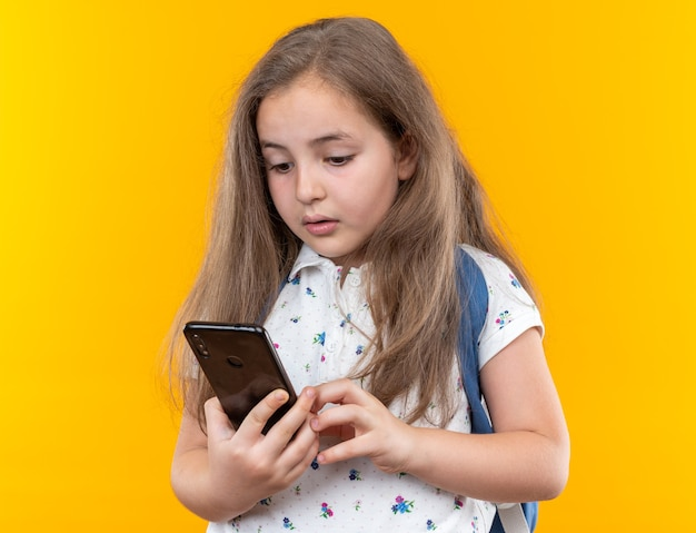Little beautiful girl with long hair with backpack holding smartphone looking at it with serious face standing over orange wall