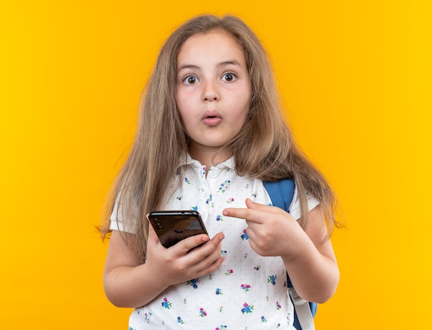 Little beautiful girl with long hair with backpack holding smartphone pointing with index finger at it being surprised looking at front standing over orange wall