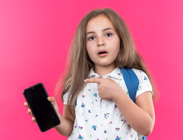 Little beautiful girl with long hair with backpack holding smartphone pointing with index finger at it surprised standing on pink