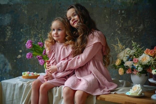 핑크 드레스에 작은 아름 다운 여자 자매
