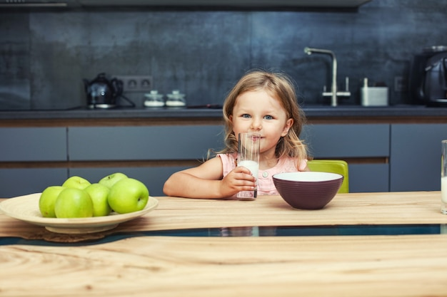 Little beautiful happy baby girl at home in the kitchen at the table with apples and milk