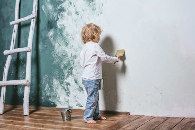Little beautiful and happy child in jeans and barefoot paint the wall with brush at home