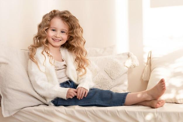 ソファに座っている小さな美しい幸せな女の子
