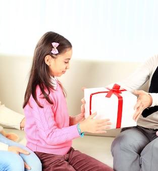 Маленькая красивая красивая девушка делает подарок своей счастливой матери