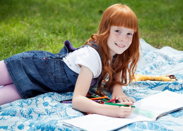 Маленькая красивая улыбающаяся девочка, рисование карандашами на плед на траве