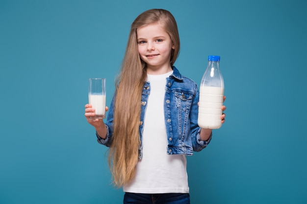 Little beauty girl in jean jacket with long brown hair hold milk container