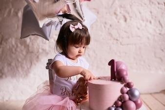 小さな誕生日の女の子ピンクのドレスの魅力的な赤ちゃんが椅子に座る