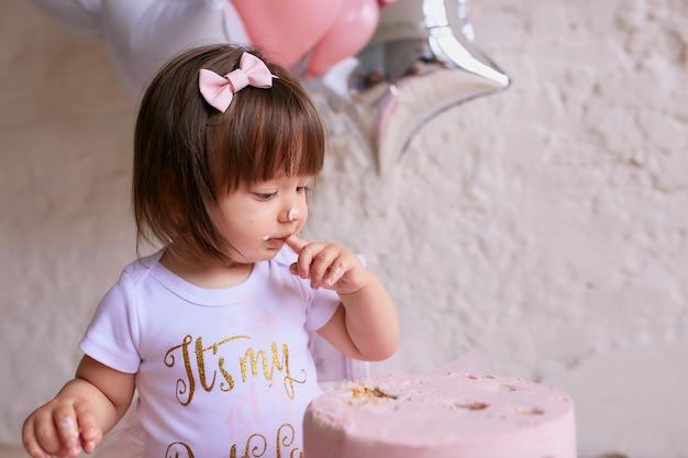 작은 생일 소녀. 핑크 드레스에 매력적인 아기는 의자에 앉아 무료 사진