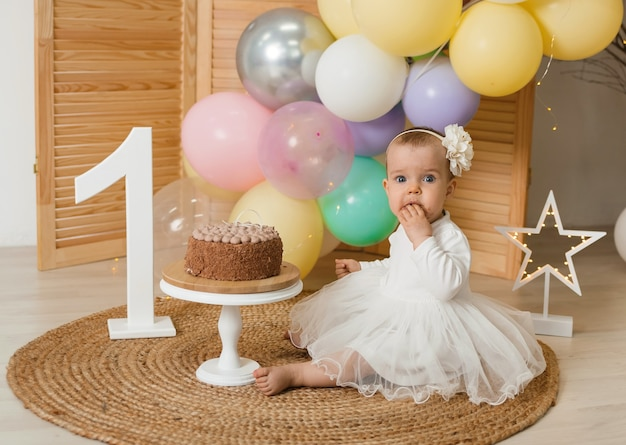 Little birthday girl in a white dress and a headband sits and eats a cake with cream hands on a festive wall with a wooden number one