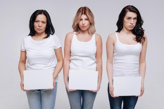 Немного расстроился. художественные довольно потрясающие дамы играют на съемочной площадке, держа белые листы бумаги и стоя рядом друг с другом