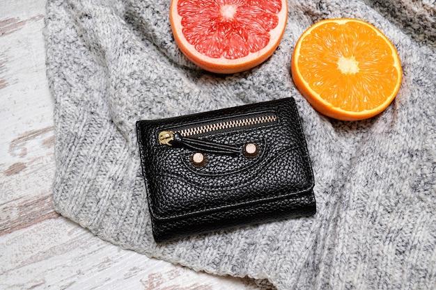 小さな黒い女性の財布と、セーターに柑橘類。ファッショナブルなコンセプト。