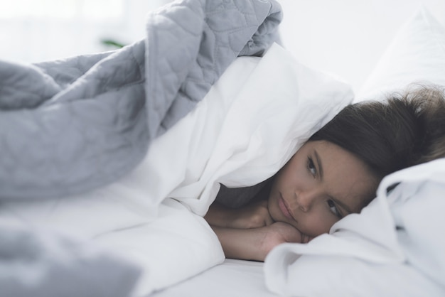 A little black girl lies in a white bed under a white blanket